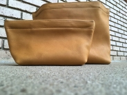 small and large desert tan leather clutches